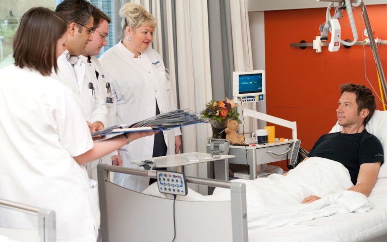 Patient_in_bed_with_medical_team_Heidelberg